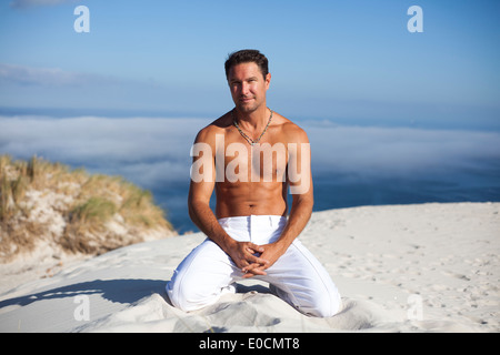 Well built white male siting on a dune, high up above the the fog rolling in on the ocean - Stock Photo