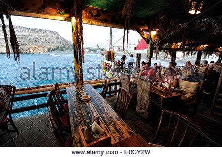 People at a bar on the beach of Matala, south coast of the greek island Crete, Mediterranean Sea, Greece, Europe - Stock Photo