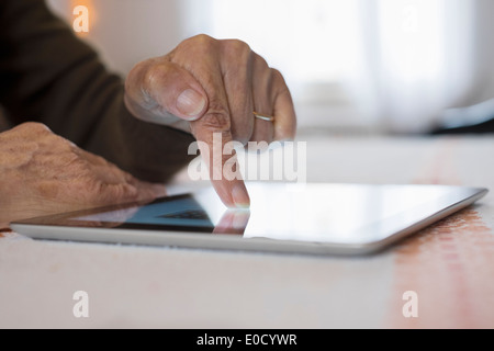 Female mature writing digital tablet indoors closeup - Stock Photo