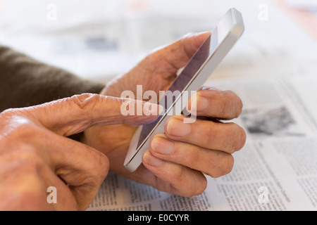 Female mature writing cell phone indoors closeup - Stock Photo