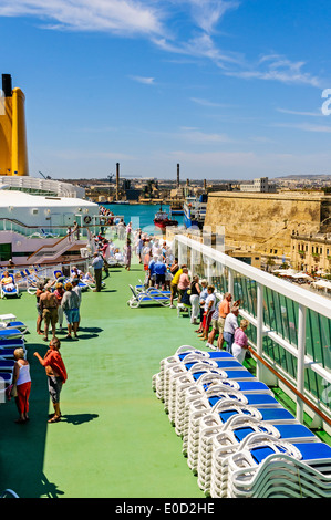 Passengers, bathed in brilliant sunshine, watch from the sun deck of the luxury cruise ship Aurora as it sails into - Stock Photo