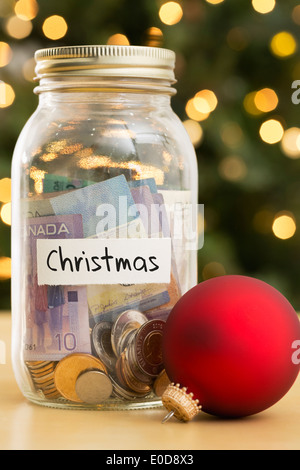 Jar filled with money labeled Christmas and Christmas ornaments lying beside - Stock Photo
