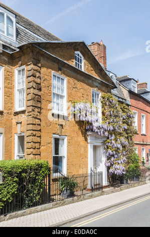 Traditional Cotswold stone town house in Shipston-on-Stour, Warwickshire, with purple wisteria growing round the - Stock Photo
