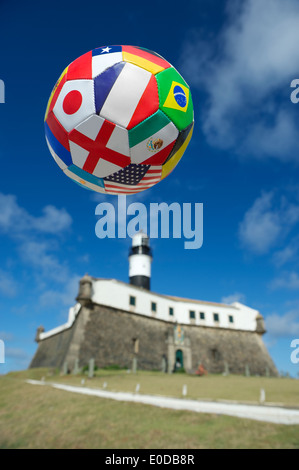 International team flag football soccer ball flying in blue sky above famous lighthouse in Barra Salvador Brazil - Stock Photo