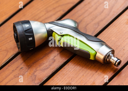 a revolver watering nozzle on a wooden table in the backyard - Stock Photo