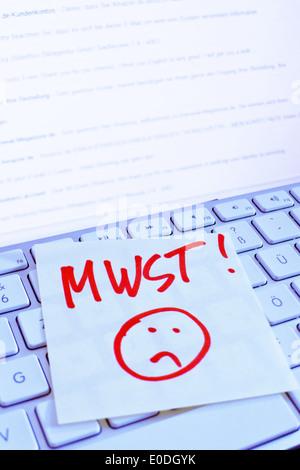 A note slip of paper lies on the keyboard of a computer in memory: VAT, Ein Notizzettel liegt auf der Tastatur eines - Stock Photo