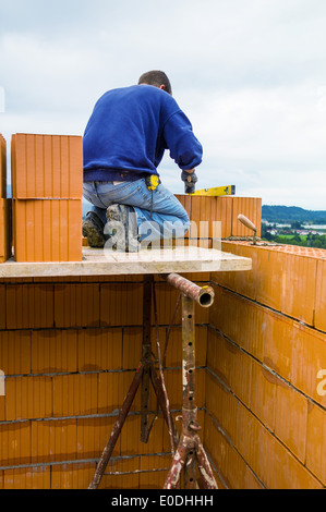 Anonymous construction worker on a building site with the building of a house establishes a wall from brick. Brick - Stock Photo
