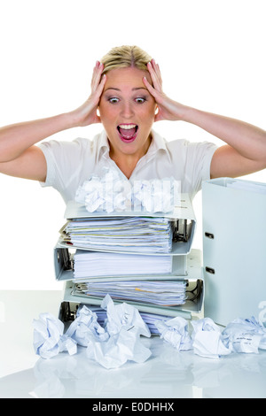 A young woman despairs in the office between many files and crumpled up paper. Symbolic photo for stress, Burnout - Stock Photo