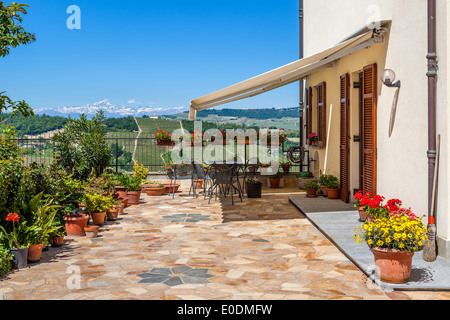 Flowers in the pots on house terrace with beautiful view on hills and mountains of Piedmont, Northern Italy. - Stock Photo