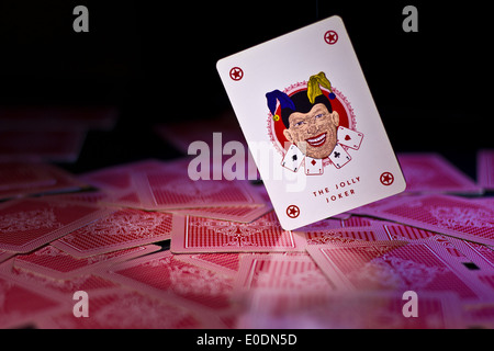 joker card falling on a spreaded deck - Stock Photo