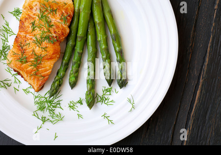 Salmon fillet with asparagus and dill on white plate dark rough wood - Stock Photo