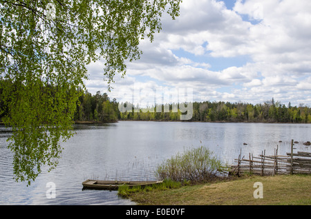 Old-fashioned lake view with a rowing boat at springtime - Stock Photo