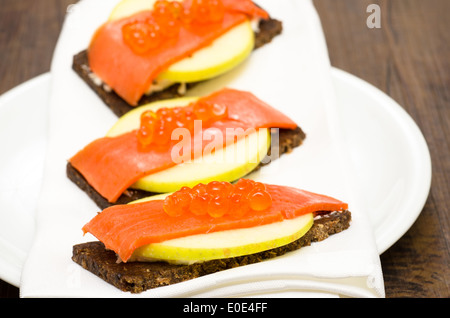 Canapes with wild salmon, caviar and apple slice - Stock Photo