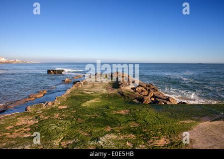 Algae covered pier on the Atlantic Ocean in Estoril, Portugal. - Stock Photo