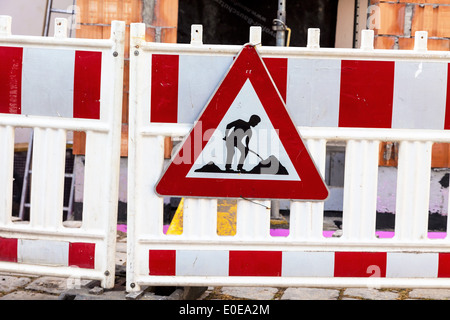 Security of the street with a building site. Sign with construction worker, Absicherung der Strasse bei einer Baustelle. - Stock Photo