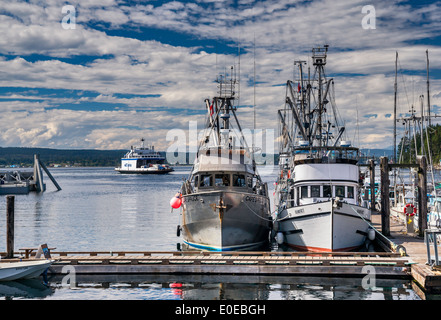 Fishing boats at marina, ferry in dist, going to Campbell River from Quathiaski Cove on Quadra Island, British Columbia, - Stock Photo