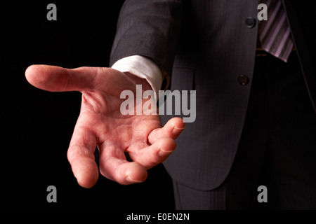 A businessman holding out his hand to shake the hand of another. - Stock Photo