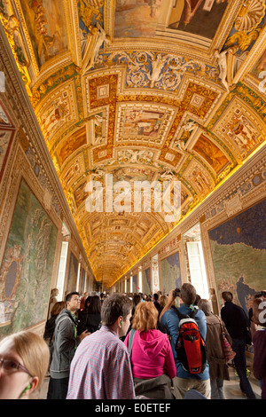 Tourists looking at the ornate decorated ceiling, the Gallery of Maps, Vatican Museum, Vatican City, Rome Italy - Stock Photo