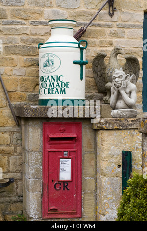Giant milk churn with old fashioned post box set in a wall and a stone gargoyle - Stock Photo