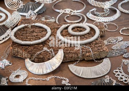 silver bracelets on driftwood tree - Stock Photo