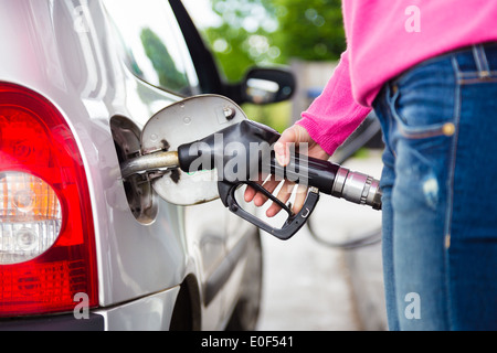 Lady pumping gasoline fuel in car at gas station. - Stock Photo