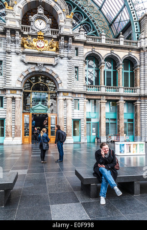 Young woman talks on her mobile phone at Antwerpen-Centraal railway station. - Stock Photo