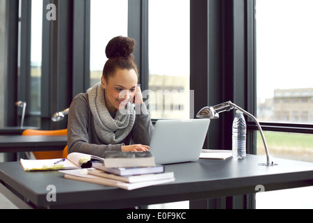 Pretty young woman sitting in library using laptop smiling. Young woman sitting at table surfing Internet for notes - Stock Photo