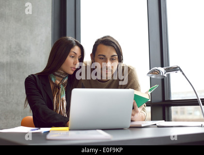 Young university students searching information in books and laptop for their studies. Sitting at the table studying - Stock Photo