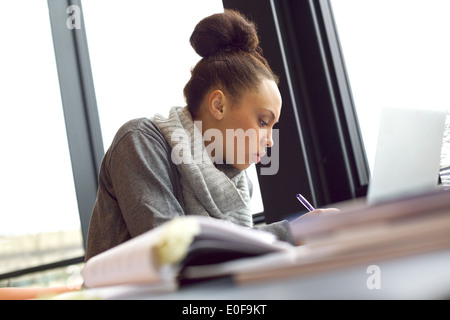 Young african american woman taking notes from books for her study. Sitting at table with books and laptop for information. - Stock Photo