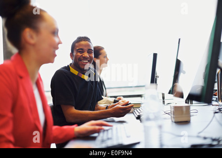 Young afro american man looking at camera smiling while working on computer in modern classroom. Young students - Stock Photo