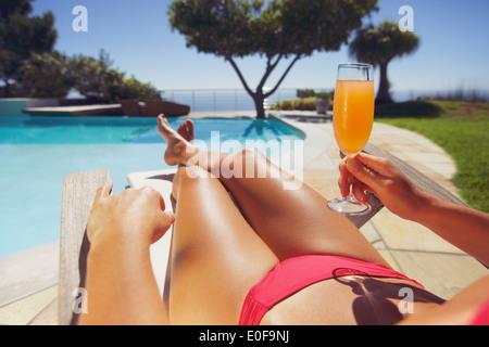 Tanned young woman in bikini with fruit juice sitting on a deck chair enjoying sunbath near swimming pool - Stock Photo