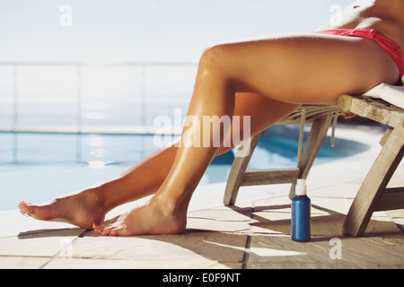 Young female relaxing on lounge chair with a suntan spray by the pool. Young lady sunbathing by the swimming pool. - Stock Photo