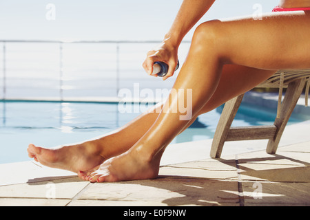 Woman applying suntan spray onto her legs. Female sitting on recliner chair by the swimming pool sunbathing. - Stock Photo