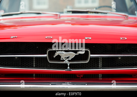 Ford Mustang horse logo on the radiator grill of this classic American car - Stock Photo