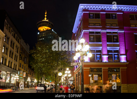 Nightlife in Gastown,Vancouver by the historic Steam Clock on Water Street.  Harbour Centre Lookout tower, buildings - Stock Photo