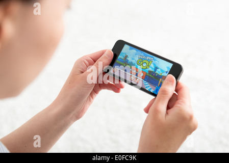 Woman playing Angry Birds Go! a kart racing mobile game application on brand new Apple iPhone 5s - Stock Photo