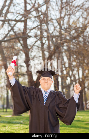 Mature male graduate gesturing happiness in park with a diploma in hand - Stock Photo