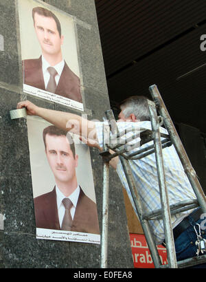 Damascus, Syria. 12th May, 2014. A worker puts up election posters in Damascus, Syria, May 12, 2014. A day earlier, - Stock Photo
