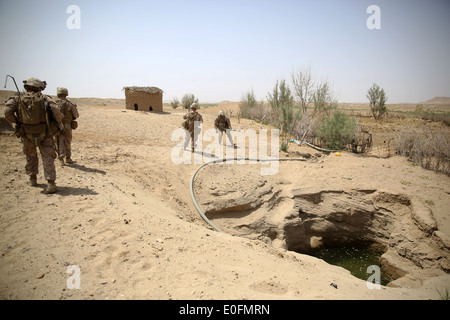 US Marines with the Bravo Company assault force speaks patrol on the outskirts of a village during a counter insurgency - Stock Photo
