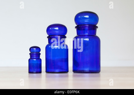 Blue glass jars isolated on a wooden table - Stock Photo