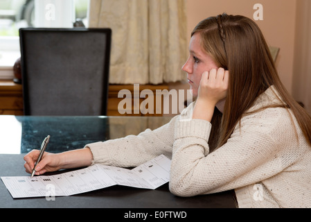 Teenage first time voter with her postal ballot paper for European Parliament election May 2014 with 15 parties - Stock Photo