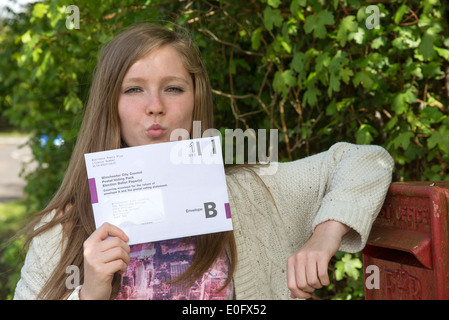 Young voter kissing her postal vote goodbye at the postbox - Stock Photo