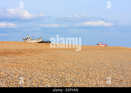 High and dry fishing boats beached on a shingle beach at Dungeness Kent - Stock Photo