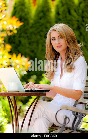 Young woman works with laptop in the garden, Junge Frau arbeitet mit Laptop im Garten - Stock Photo
