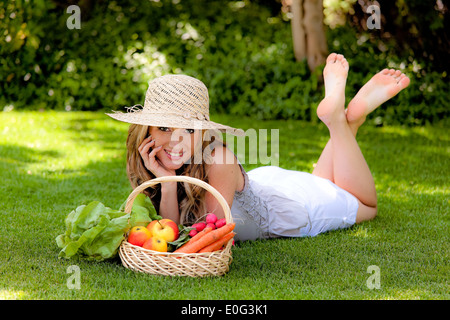 young woman with fruit and vegetables in the basket, junge Frau mit Obst und Gemuese im Korb - Stock Photo