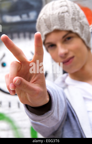 A cool looking youthful man before graffiti, Ein cool blickender Jugendlicher Mann vor Graffiti - Stock Photo