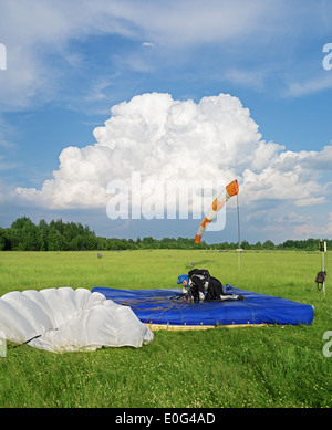 One day with parachutist in airfield. The skydiver landing under white parachute. - Stock Photo