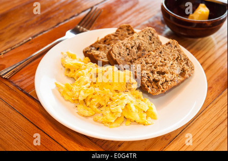 Plate of scrambled eggs and banana bread on a wooden table with a dish of butter - Stock Photo