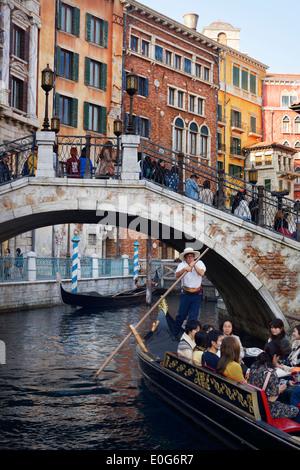 People taking a ride in a Venetian gondola passing under a bridge at Tokyo Disneysea Mediterranean harbor. Japan. - Stock Photo