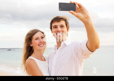 Happy young couple taking a selfie on the beach at sunset - Stock Photo